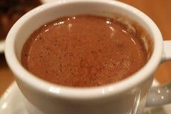 Fechado acima do chocolate quente mouthwatering em um copo branco com foco seletivo e fundo borrado foto de stock
