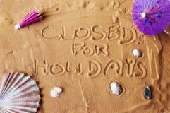 Fechado por os feriados escritos na areia Imagem de Stock Royalty Free