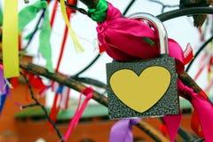 Fechadura da porta com um coração pendurado em uma árvore com as fitas para a boa sorte imagens de stock