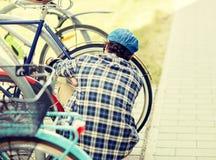 Fechamento da bicicleta da asseguração do homem no estacionamento da rua foto de stock