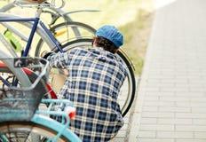 Fechamento da bicicleta da asseguração do homem no estacionamento da rua fotografia de stock