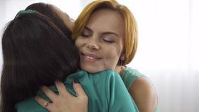 Fechamento de jovens mulheres caucasianas felizes em vestidos leves abraçando-se firmemente Garota ruiva abraçando sua amiga gráv filme