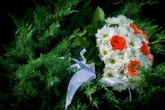 Fechamento do casamento do ouro nas mãos do par Noiva que guarda um ramalhete brilhante do casamento com diferente foto de stock royalty free