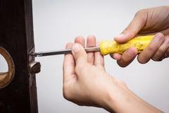 Fechamento do reparo do serralheiro na porta de madeira Foto de Stock