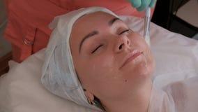 Fechamento O cosmetólogo aplica um gel nutritivo na face de uma linda garota com uma escova Mão de mulher na luva verde Rej filme