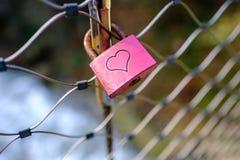Fechamento vermelho com um símbolo do coração em uma ponte de corda Fotografia de Stock