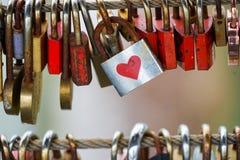 Fechamentos coloridos que penduram na ponte para o amor Foto de Stock