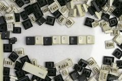 Fechando trabalhos em microstocks, as palavras-chaves da palavra dobradas das chaves do teclado velho fotografia de stock royalty free