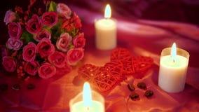Fechar día de San Valentín con la flor de la decoración y la cantidad ardiente de la vela