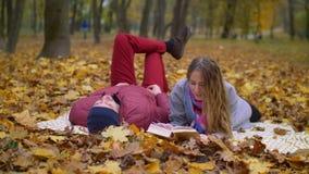 Fechar los pares que leen un libro en naturaleza del otoño almacen de metraje de vídeo