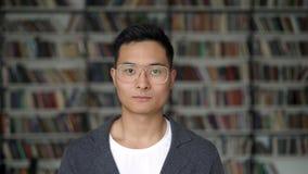 Fechar o retrato de um jovem asiático ao fundo das prateleiras da biblioteca video estoque