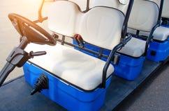Feche acima atrás da roda de um carrinho de golfe estacionado no pavimento fotografia de stock royalty free