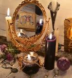Feche acima com espelho mágico e velas pretas Fotografia de Stock Royalty Free