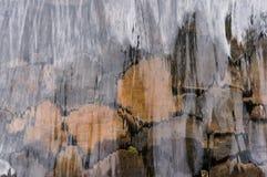 Feche acima da água de fluxo sobre a parede da rocha fotografia de stock royalty free