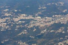 Feche acima da aldeia da montanha de Gangtok com árvores verdes e o céu azul que veem o nível superior do formulário do monastéri Fotografia de Stock