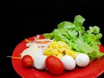 Feche acima da alface, do ovo, do tomate, do milho e da maionese frescos na placa vermelha fotografia de stock royalty free