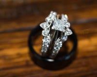 Feche acima da aliança de casamento das noivas que senta-se na aliança de casamento dos noivos imagens de stock