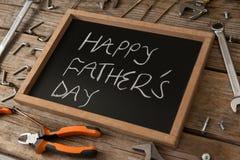 Feche acima da ardósia com texto feliz do dia de pais entre ferramentas da mão imagens de stock royalty free