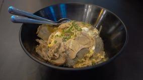 Feche acima da bacia da cozinha com a omeleta quente e a carne de porco do arroz fritado na tabela Foo tailandês filme