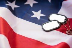 Feche acima da bandeira americana e dos crachás militares Imagem de Stock