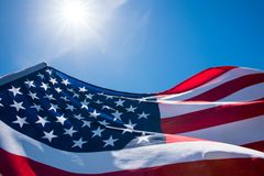Feche acima da bandeira do Estados Unidos da América no fundo do céu azul imagens de stock royalty free