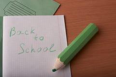 Feche acima da bandeja verde grande que encontra-se no caderno com texto de volta à escola na tabela fotografia de stock