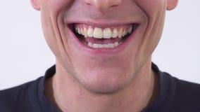 Feche acima da boca de tiro do homem louco está sorrindo no sorriso insalubre largo Tiro em um fundo branco vídeos de arquivo