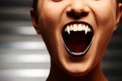 Feche acima da boca de uma mulher do vampiro Foto de Stock Royalty Free