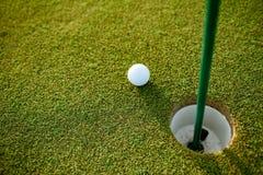 Feche acima da bola de golfe ao lado do furo foto de stock