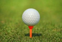 Feche acima da bola de golfe branca no T alaranjado na grama verde foto de stock