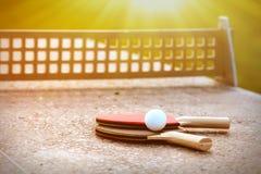 Feche acima da bola de tênis de mesa com as raquetes de tênis na tabela de pedra em luzes ensolaradas, equipamento do tênis para  Fotos de Stock Royalty Free
