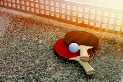 Feche acima da bola de tênis de mesa com as raquetes de tênis na tabela de pedra em luzes ensolaradas, equipamento do tênis para  Fotografia de Stock