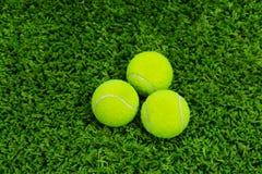 Feche acima da bola de tênis na grama Imagens de Stock Royalty Free