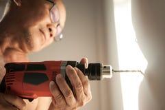 Feche acima da broca, ancião que usa uma ferramenta elétrica da perfuração Fotos de Stock Royalty Free