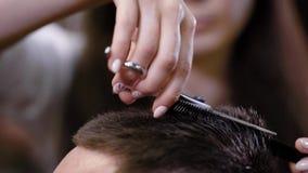 Feche acima da cabeça e das mãos masculinas de extremidades fêmeas do cabelo do corte do barbeiro do cliente que usa o pente e o  filme