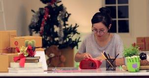 Feche acima da caixa de presente de entortamento da menina bonito asiática e de escrever o cartão feliz com cara do sorriso filme