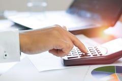 feche acima da calculadora e do contador da imprensa da mão que olham o caderno, fotos de stock royalty free