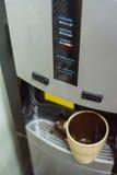 Feche acima da caneca do chá no refrigerador de água moderno Imagens de Stock