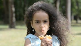 Feche acima da cara da criança, retrato africano da menina que come o Hamburger enorme com apetite no parque urbano no verão ou n filme