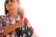 Feche acima da cara séria da mulher coberta pela bandeira dos EUA Foto de Stock