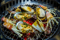 Feche acima da carne, da carne de porco, do cogumelo, do mexilhão gigante e do calamar no fogão de Yakiniku Imagens de Stock Royalty Free