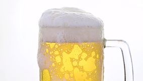 Feche acima da cerveja de cerveja pilsen de derramamento no vidro sobre o branco video estoque