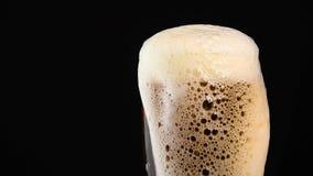 Feche acima da cerveja de cerveja pilsen de derramamento no vidro sobre o preto vídeos de arquivo