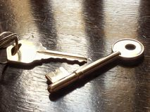 Feche acima da chave da porta com fundo de madeira da tabela Foto de Stock