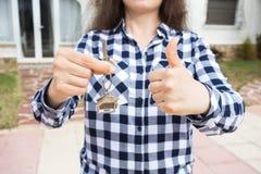 Feche acima da chave da terra arrendada da mulher com um keychain na forma da casa e mostrar os polegares acima Chave da casa no  imagem de stock royalty free