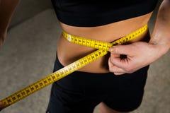 Feche acima da cintura de medição da mulher pela fita no gym Imagens de Stock