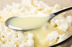 Feche acima da colher com leite condensado na bacia com requeijão imagem de stock royalty free
