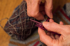 Feche acima da confecção de malhas idosa das mãos do ` s da mulher Imagens de Stock Royalty Free