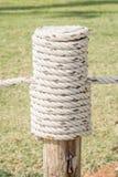 Feche acima da corda cansado no polo de madeira com o backgrou da grama verde Fotos de Stock