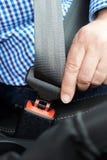 Feche acima da correia de Person In Car Fastening Seat Foto de Stock